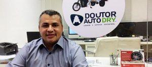 Executivo sentado no escritório com uma placa atrás escrito: Doutor auto dry lavagem e estética sustentável