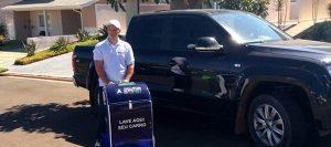 Carro preto atrás de um franqueado com o carrinho delivery da Doutor auto dry