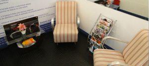 Dois sofás, mesa de canto e revisteiro na recepção de uma loja DryUp