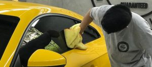 Profissional fazendo a remoção de mancha no vidro do carro