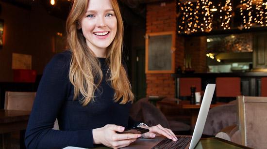 Mulher sentada em uma mesa mexendo no notebook e no celular à procura de franquias até R$ 100 mil